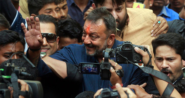 Bollywood actor Sanjay Dutt centre, waves to his fans as he arrives at his residence in Mumbai, India